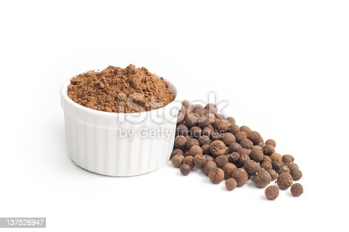 Allspice whole ,beside ground allspice in small white bowl isolated on white background