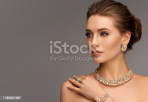 Portrait of alluring woman dressed in a posh jewelry set of necklace, ring and earrings. Pretty model is gazing at the viewer by magnetic look, perfect evening makeup and hair gathered in elegant bun.