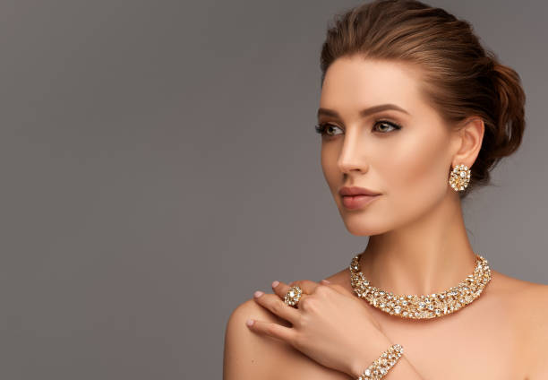 Alluring woman dressed in a posh jewelry set of necklace, ring and earrings. Elegant evening style. Portrait of alluring woman dressed in a posh jewelry set of necklace, ring and earrings. Pretty model is gazing at the viewer by magnetic look, perfect evening makeup and hair gathered in elegant bun. jewels stock pictures, royalty-free photos & images