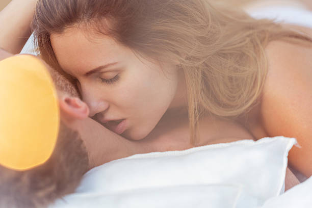 alluring woman kissing male neck - kissing on neck stock photos and pictures