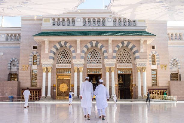 Al-Masjid Al-Nabawi or Prophet Muhammed Mosque Prayers walking in the entrance gate of Al-Masjid Al-Nabawi or Prophet Muhammed Mosque, the most beautiful mosque in the world, located in City of Medina umrah stock pictures, royalty-free photos & images