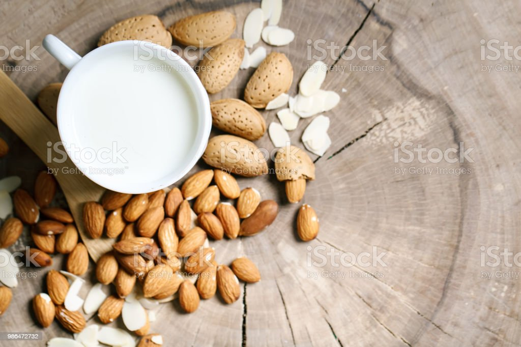 Almond and almond milk on a wooden table in the summer garden. Useful food stock photo