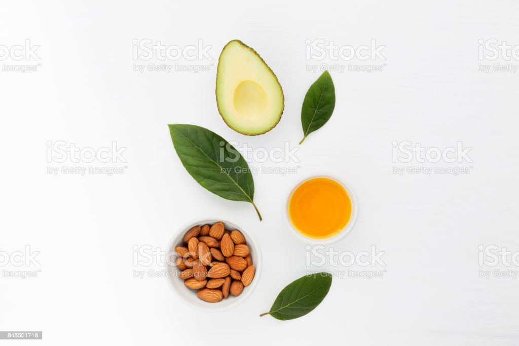 Almond and avocado oil in bowl. Skin care and hair loss ingredients. stock photo
