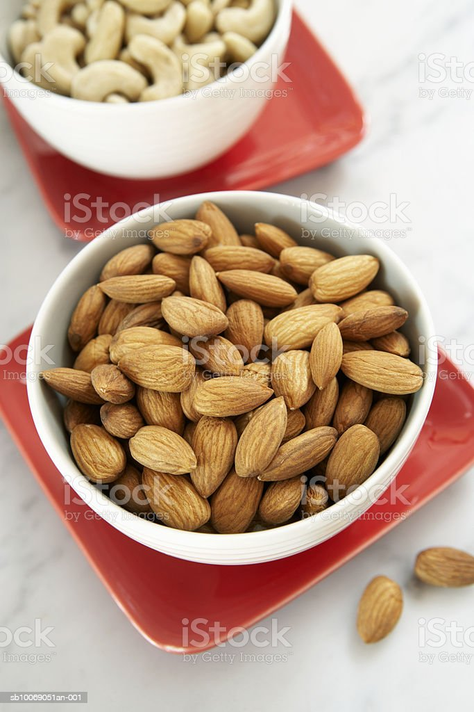 Almond and cashew nuts in bowls, close-up, elevated view royalty-free stock photo