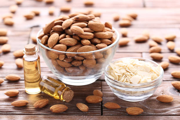 almond and oil in bottles on brown wooden table - mandorla foto e immagini stock