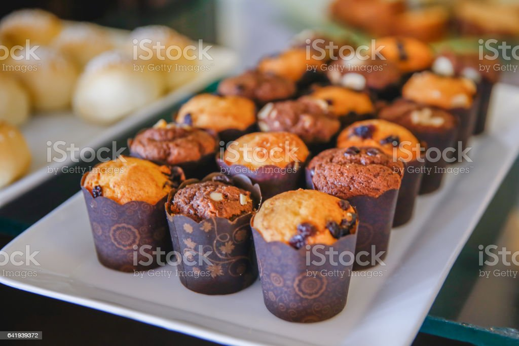 Almond and raisin chocolate muffin in bakery display stock photo