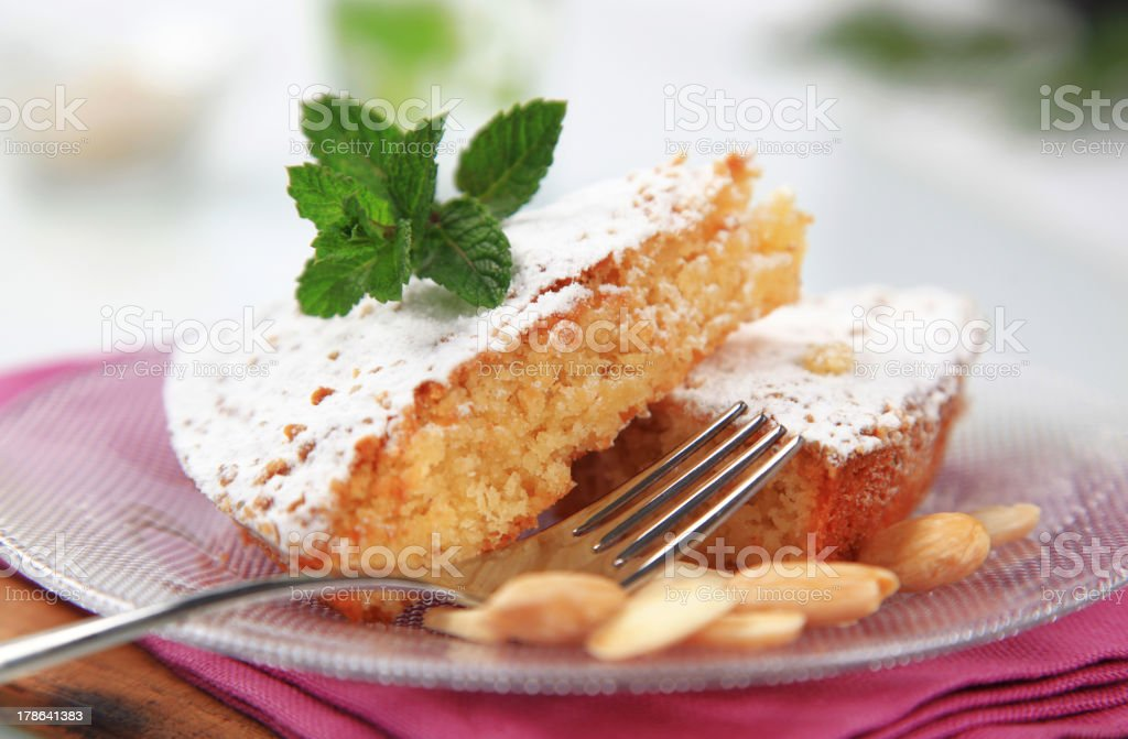 Almond cake served on glass plate with fork stock photo