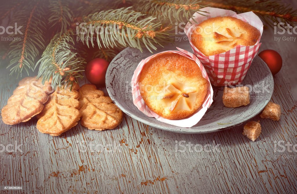 Almond cookies and lemon mini-muffin with Christmas fir twigs and baubles stock photo