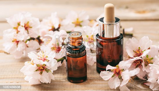 Natural cosmetics. Pink almond blossoms and essential oil containers on wooden table
