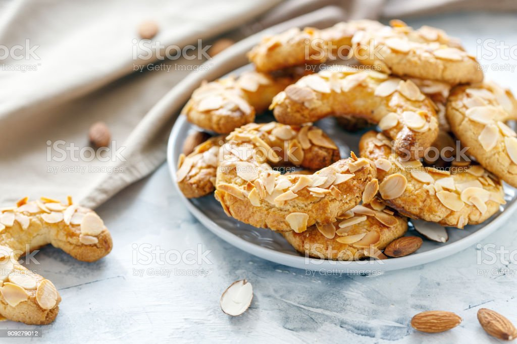 Almond crescents cookies on a white plate. stock photo