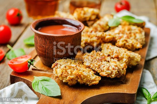 istock almond crusted chicken tenders with ketchup on a wood background 1197165999