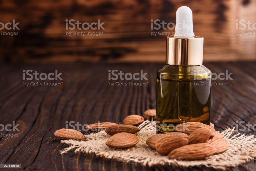 almond essential oil on a wooden background stock photo