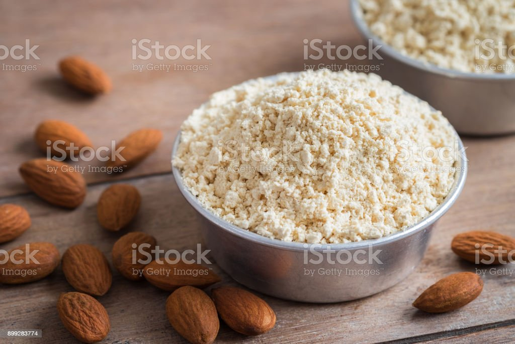 Almond flour in bowl and almonds on wooden table stock photo