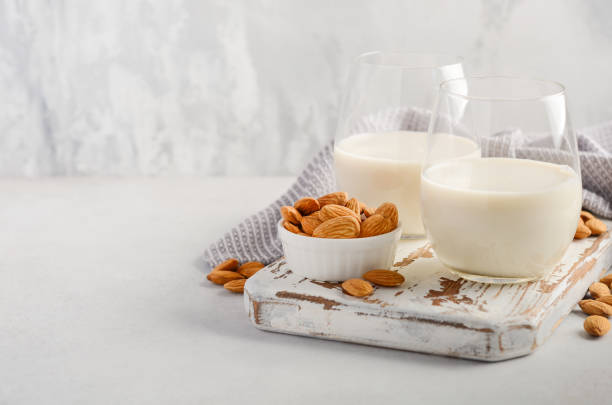 Almond milk and almonds on a white wooden cutting board. stock photo