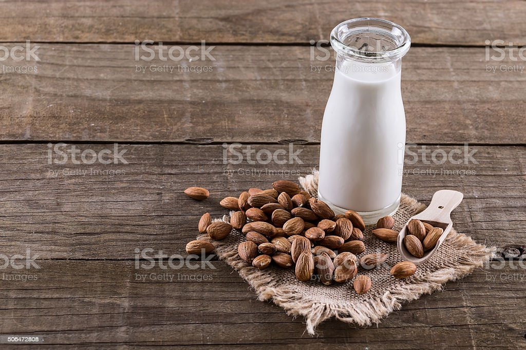 Almond milk and nuts over rustic wooden background stock photo