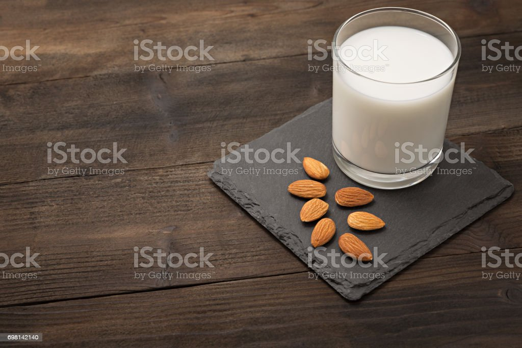 Almond milk on brown wooden background stock photo