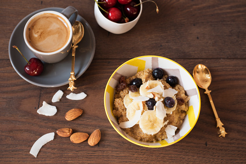 Almond Milk Quinoa With Fresh Fruits, Cherries And Coffee. Healthy Breakfast, Lifestyle Concept. Top View. Dark Wooden Background. Fitness Mood Diet. Summer Light Snack