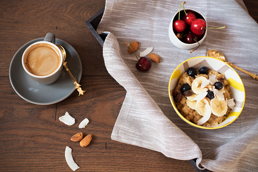 Almond Milk Quinoa With Fresh Fruits, Cherries And Coffee in a Tray. Healthy Breakfast, Lifestyle Concept. Top View. Dark Wooden Background. Fitness Mood Diet. Summer Light Snack