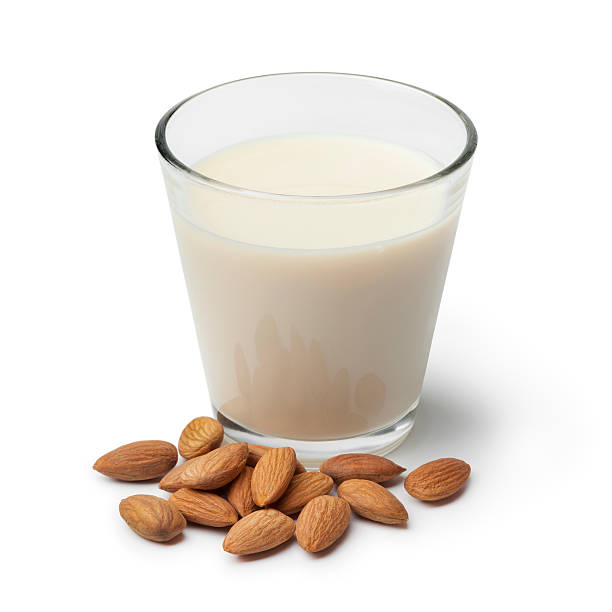 Almond milk with a heap of almonds stock photo