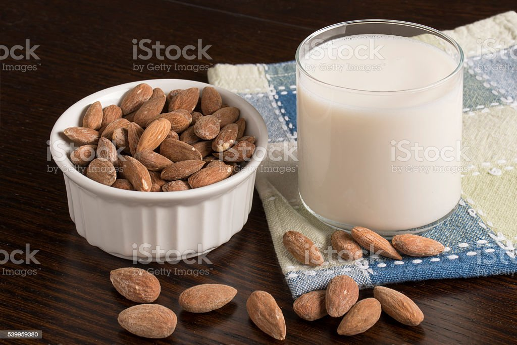 Almond Milk with almonds on table stock photo