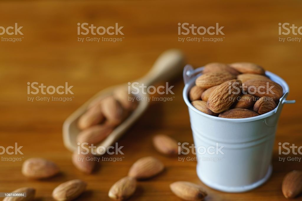 Almond nut in white can on wooden table background, copy space