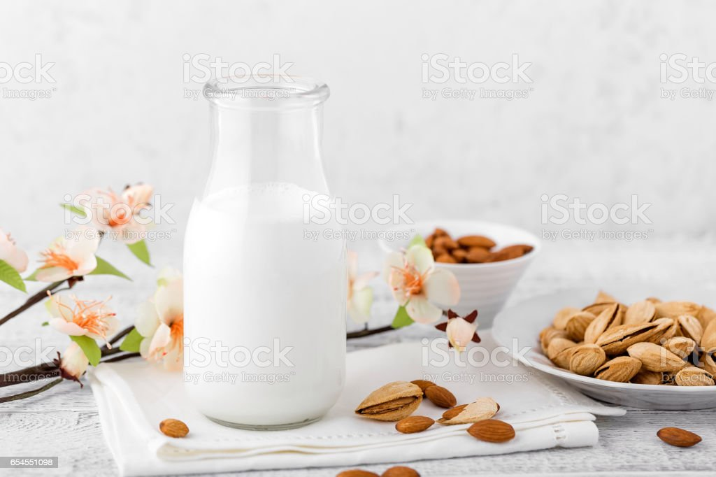 Almond nuts and milk on white background stock photo