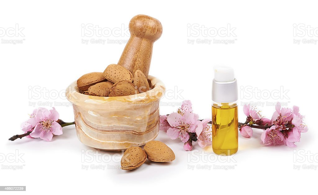 almond oil and almond nuts with flowers on white background stock photo