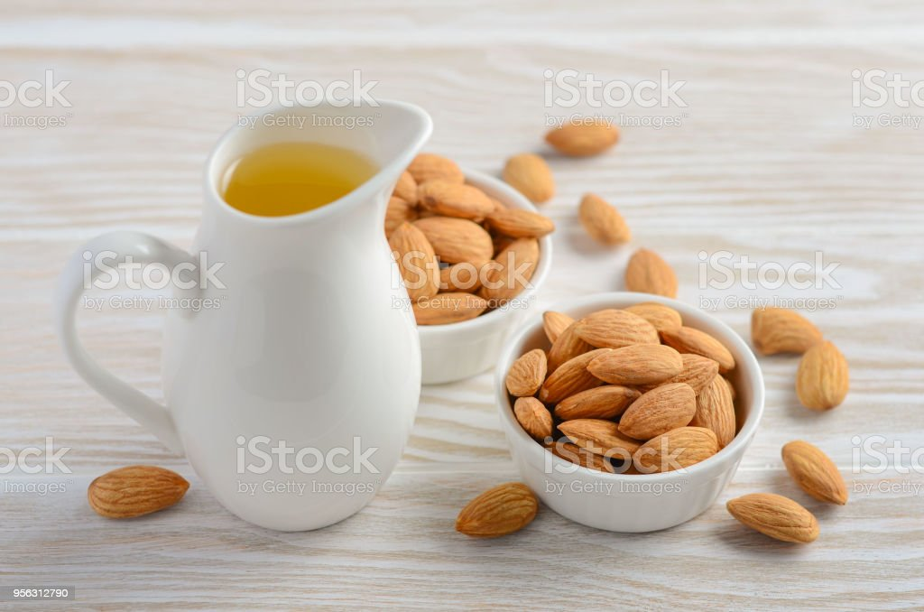 Almond oil and almonds on a white wooden background, selective focus