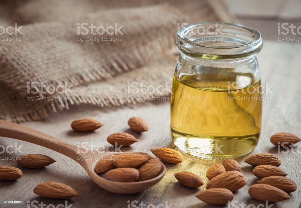 Almond oil in glass bottle and almonds on wooden table stock photo