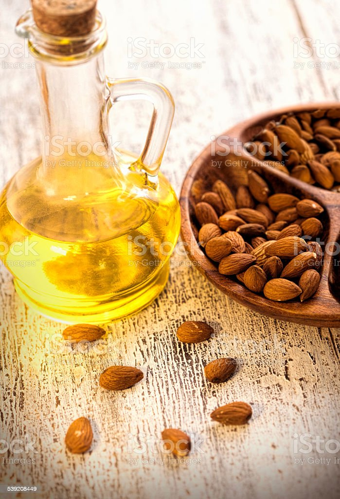 Almond oil in glass bottle and almonds stock photo