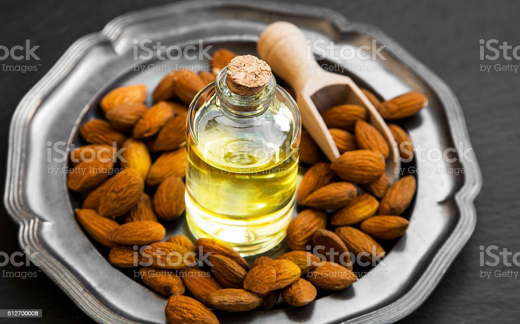 Almond oil in transparent bottle with almonds stock photo