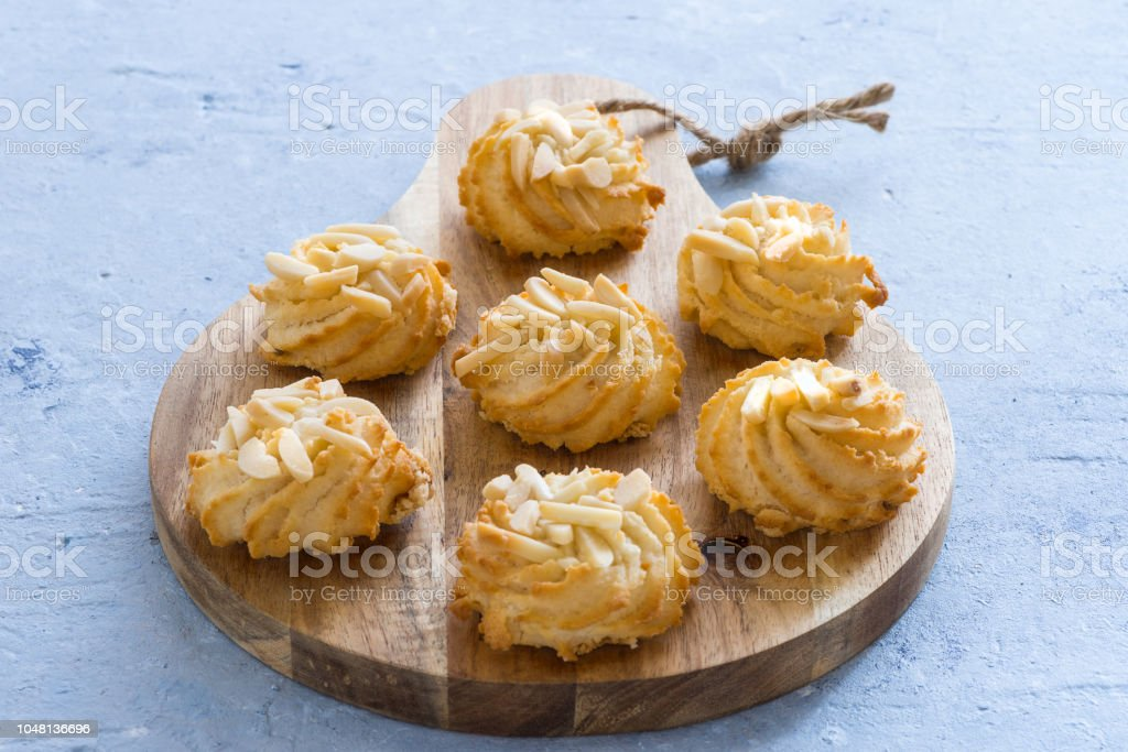 Almond pastry on chopping board on blue background - foto stock