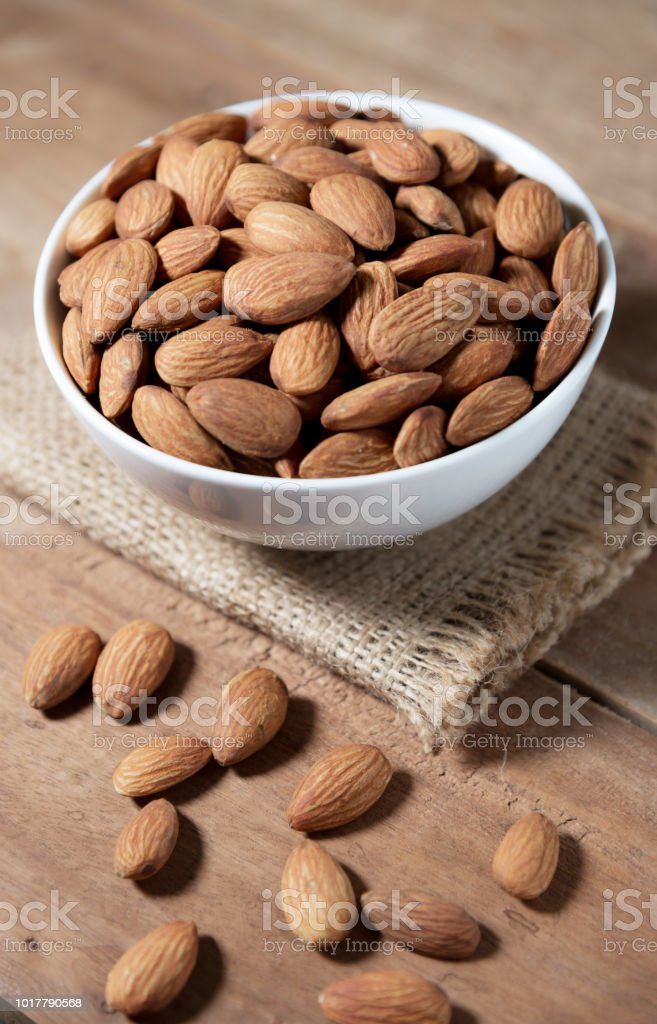Almond snack fruit in white bowl on wooden table background