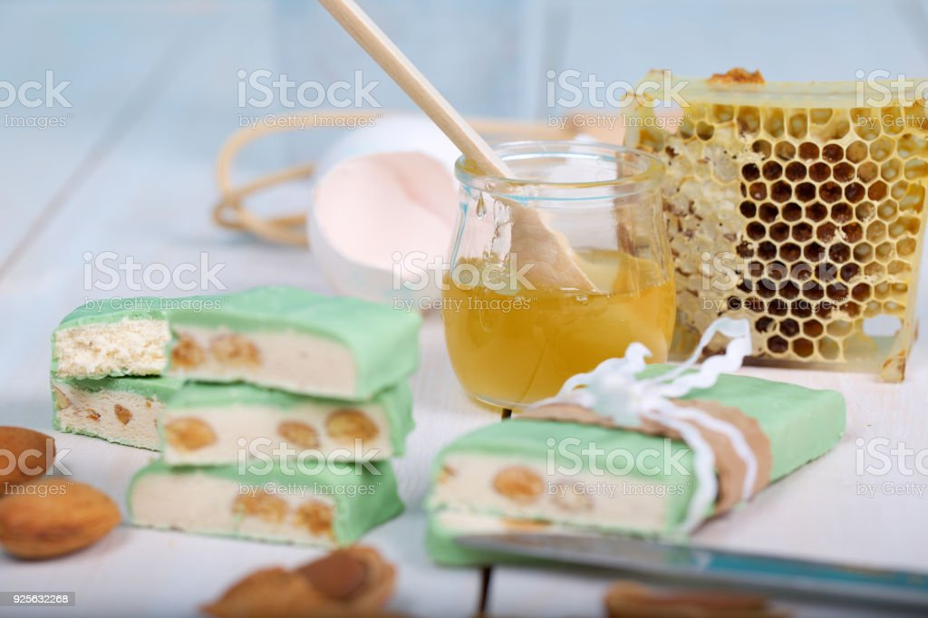 Almond turron covered by pistachio chocolate on a wooden surface. stock photo