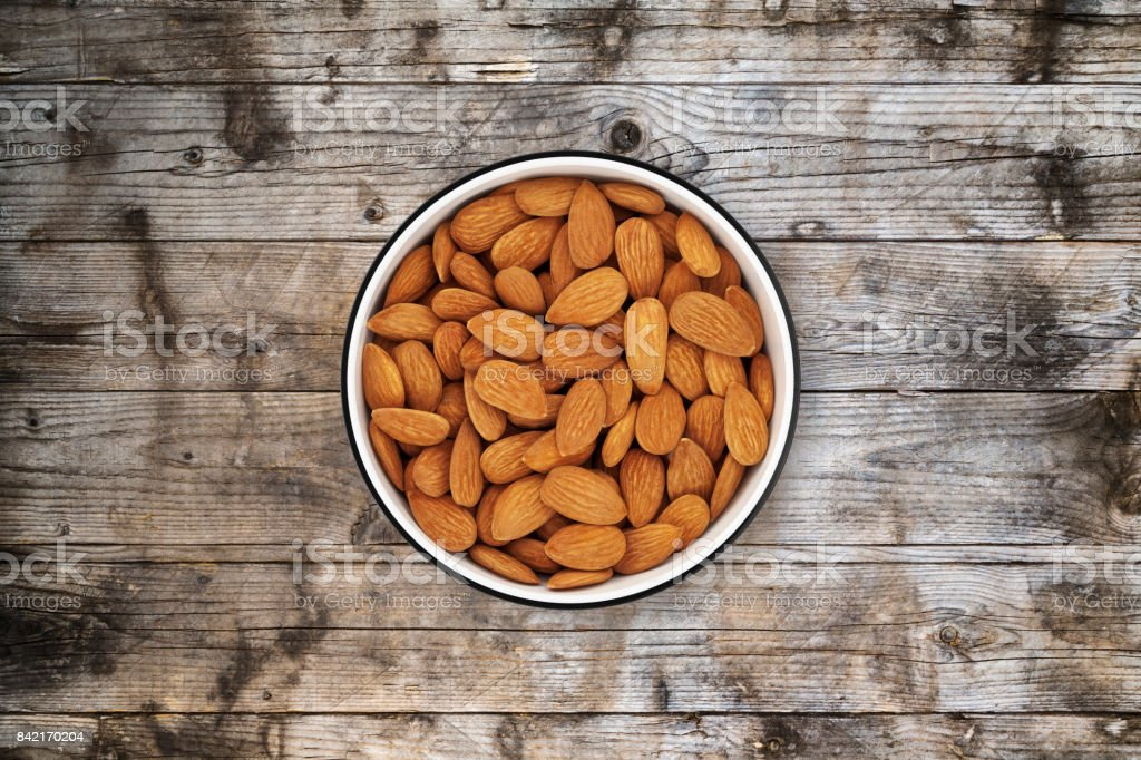 Almonds bowl on old wood background from directly above stock photo