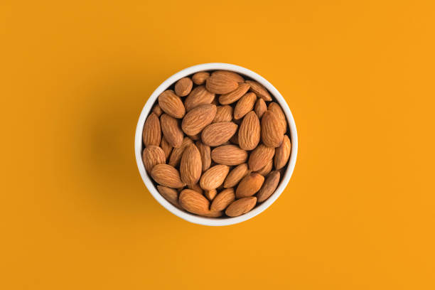 almonds in a bowl on yellow background - amendoas imagens e fotografias de stock