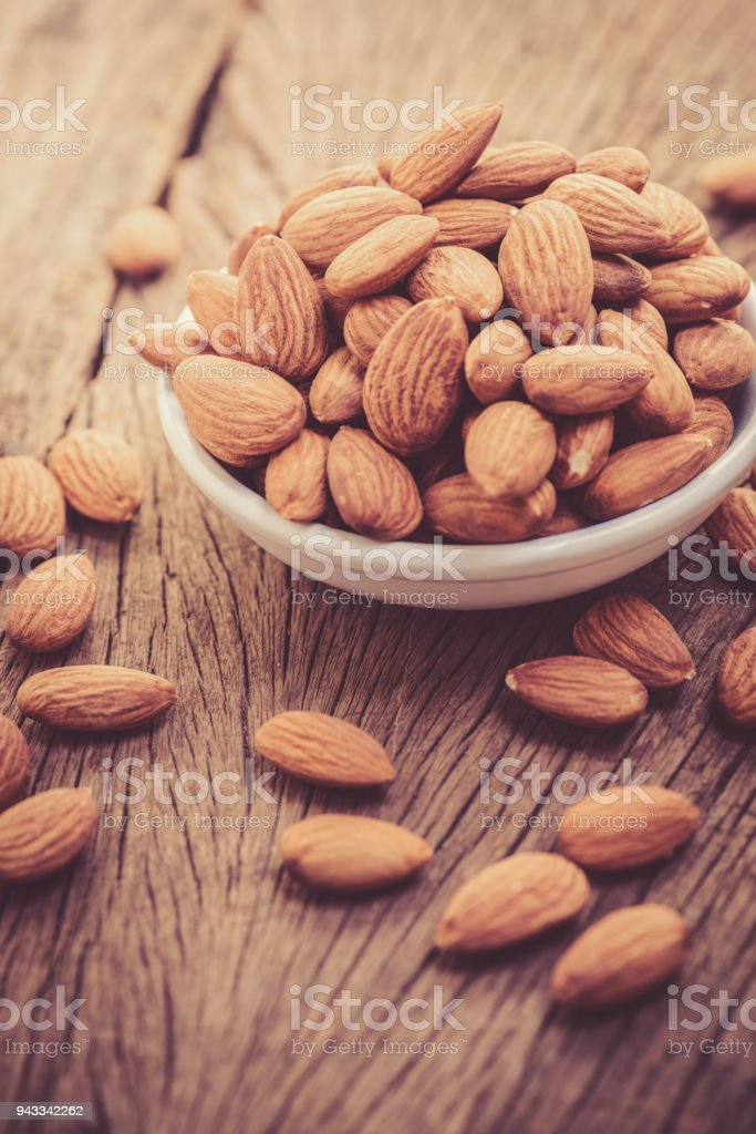almonds in a white ceramic bowl on grained wood background stock photo