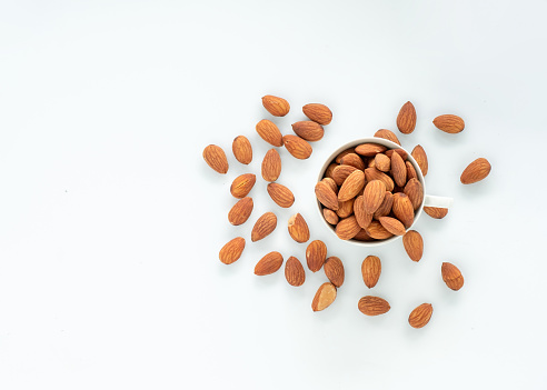 Almonds in cup with fall on white background