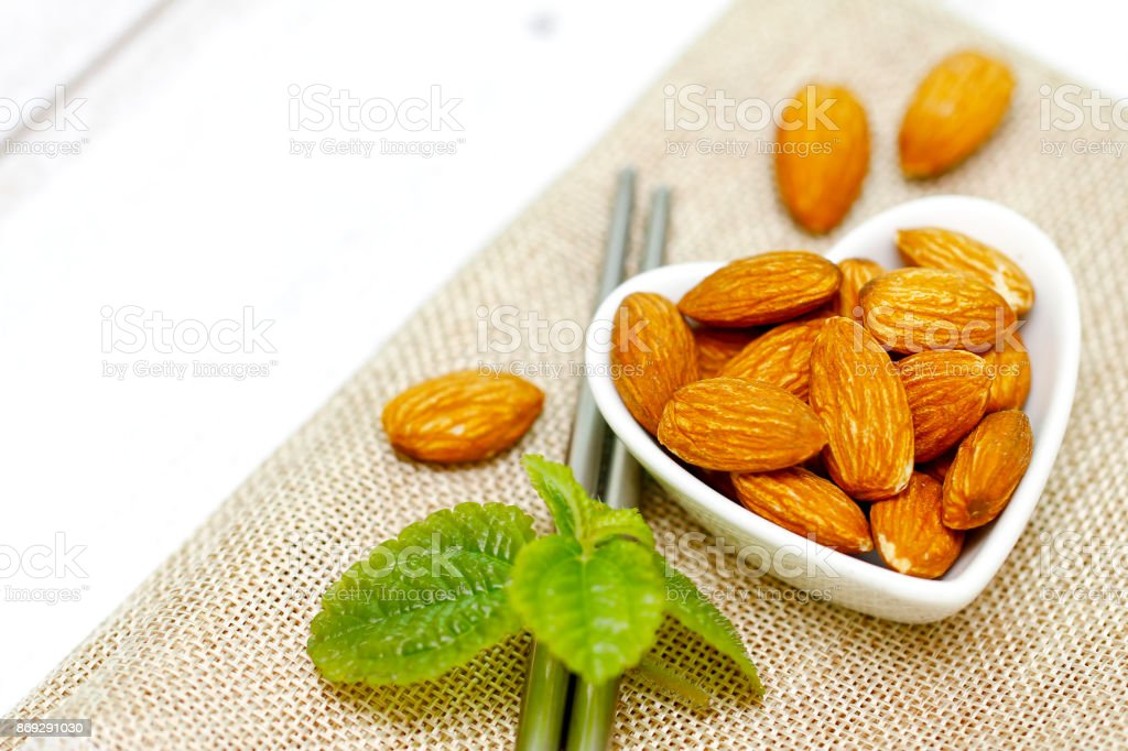 Almonds in white bowl on wooden background stock photo