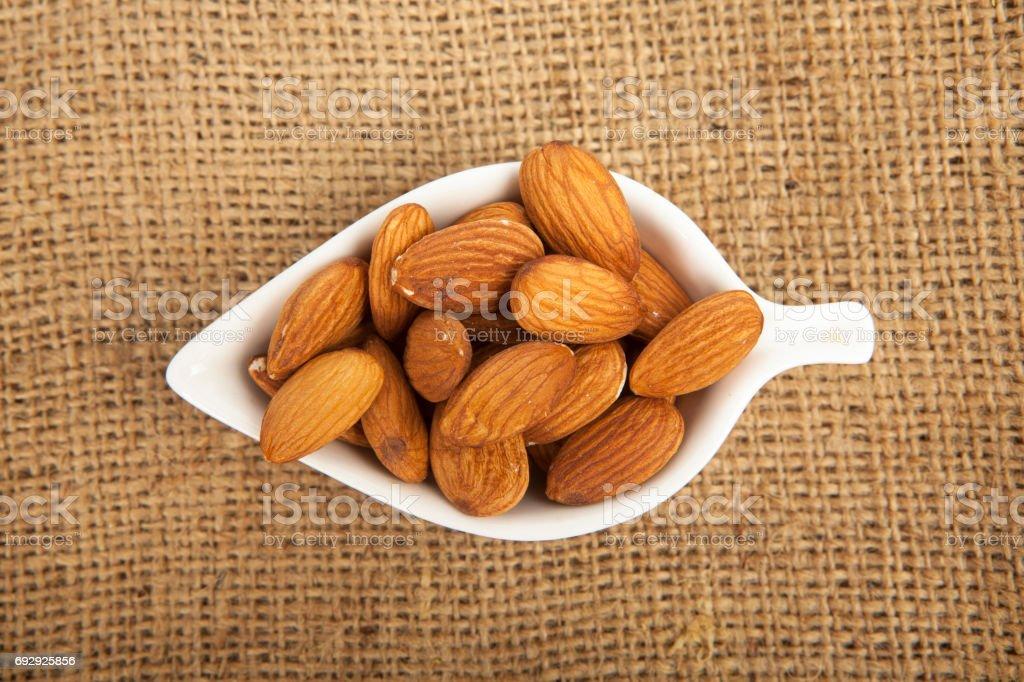 Almonds in white ceramic bowl on sack background stock photo
