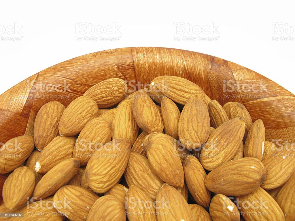 Almonds in wooden dish isolated on white background stock photo