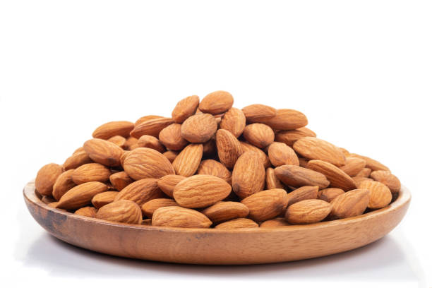 Almonds in wooden dish on white background. stock photo