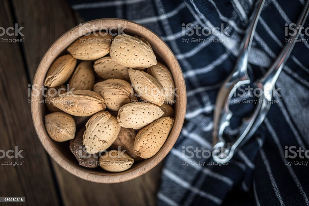 Almonds in-shell in wooden bowl. royalty-free stock photo