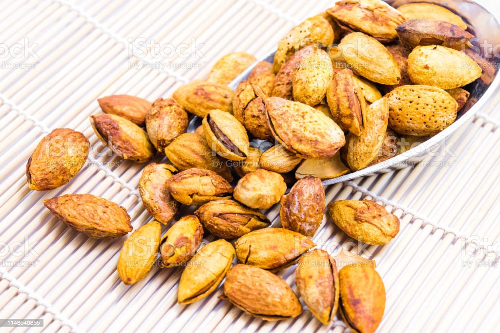 Almonds in a steel scoop isolated on white background