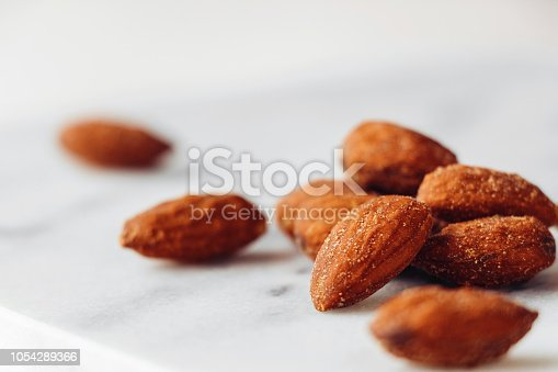 Salted and roasted almonds on a marble background, close up