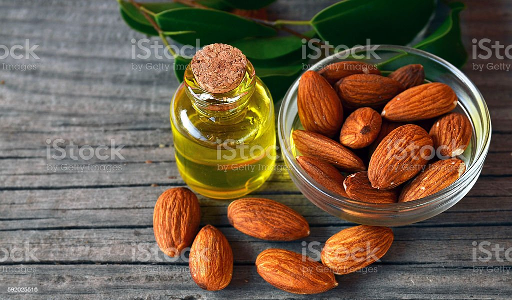 Almonds seed and almond oil on old wooden background. stock photo