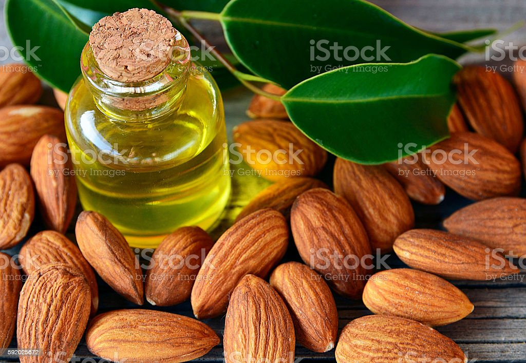 Almonds seed and almond oil on old wooden background.. stock photo
