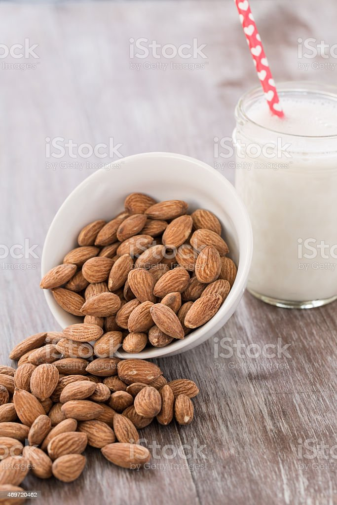 Almonds Spilling From White Bowl With Almond Milk stock photo