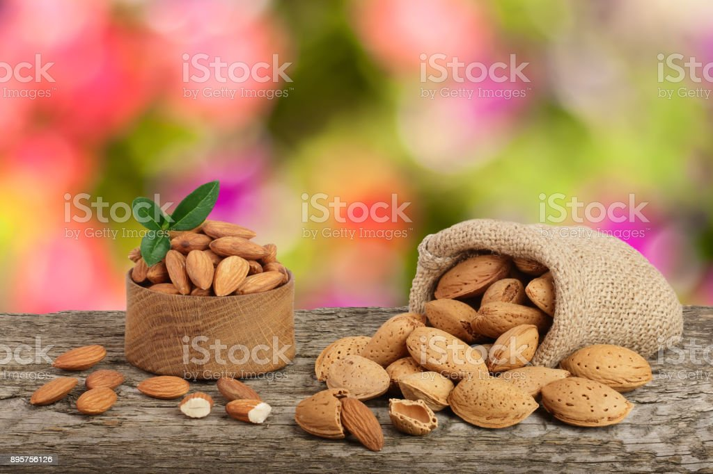 Almonds with leaf in bag from sacking on a wooden table with blurred garden background stock photo
