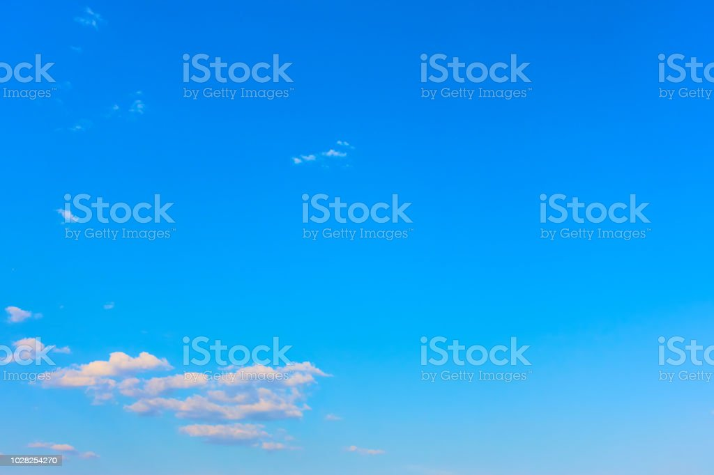 Almost clear blue sky with clouds stock photo